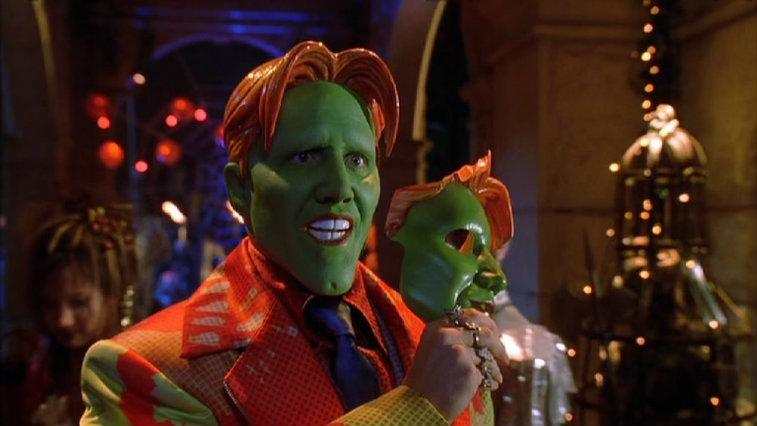 Jamie Kennedy in 'Son of the Mask' with a green face smiling and holding a masquerade-style mask