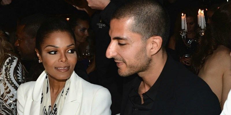 Janet Jackson is sitting next to Wissam Al Mana and is looking at him.