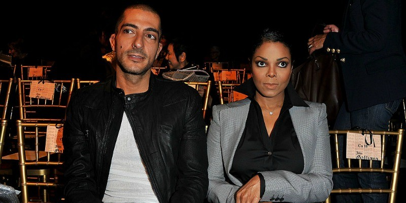Wissam Al Mana and Janet Jackson look serious as they sit front row at a fashion show.