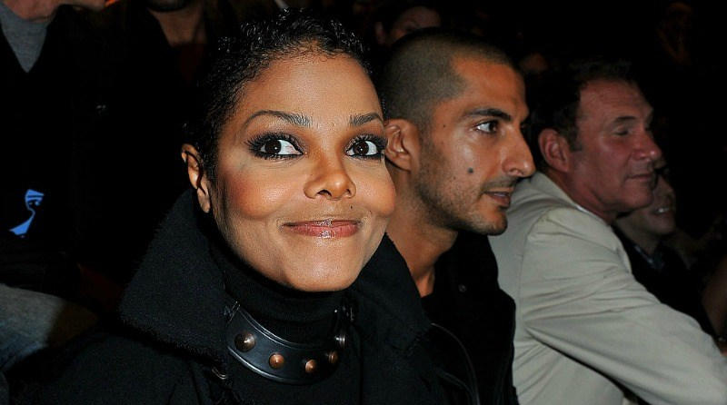 Janet Jackson gives a tight smile to the camera as she sits next to Wissam Al Mana at a fashion show.