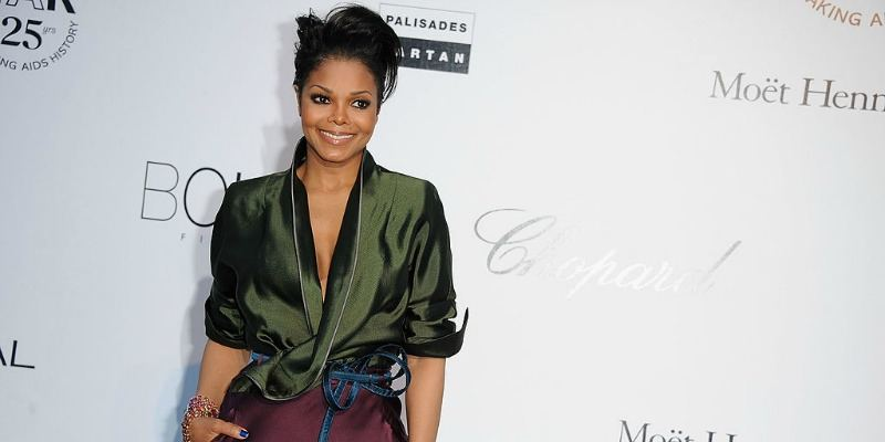 Janet Jackson on the red carpet in a green silk shirt with her hair up