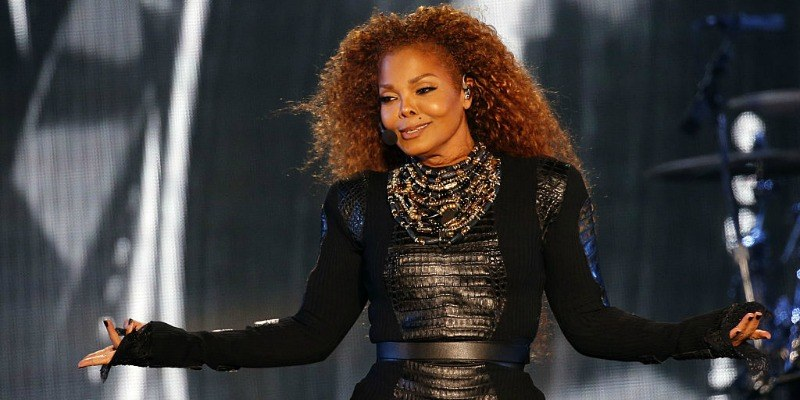 Janet Jackson in a black dress singing on stage