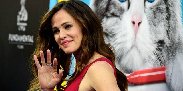 Jennifer Garner waves and is wearing a red dress on the red carpet.