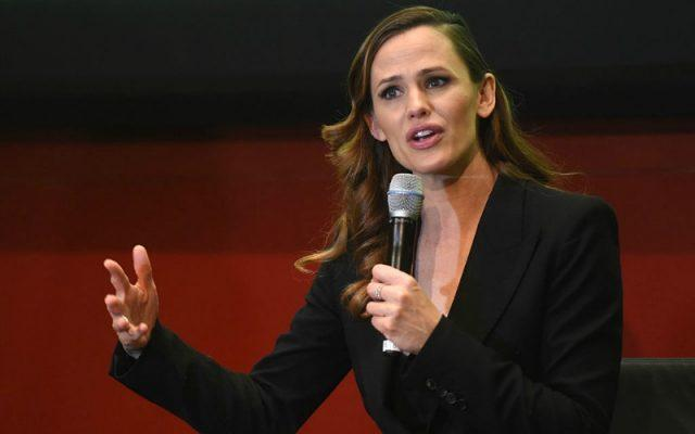 Jennifer Garner speaking into a microphone while wearing a black suit.