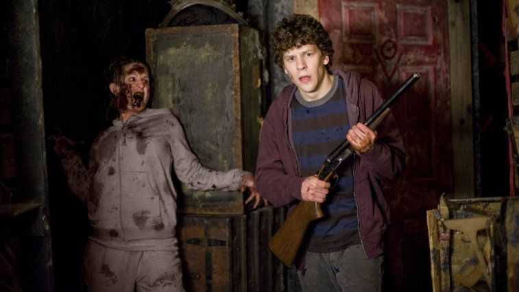 Jesse Eisenberg holding a gun as a zombie comes from behind in Zombieland
