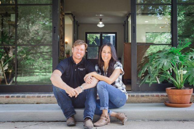 Chip and Joanna Gaines sitting on a porch.