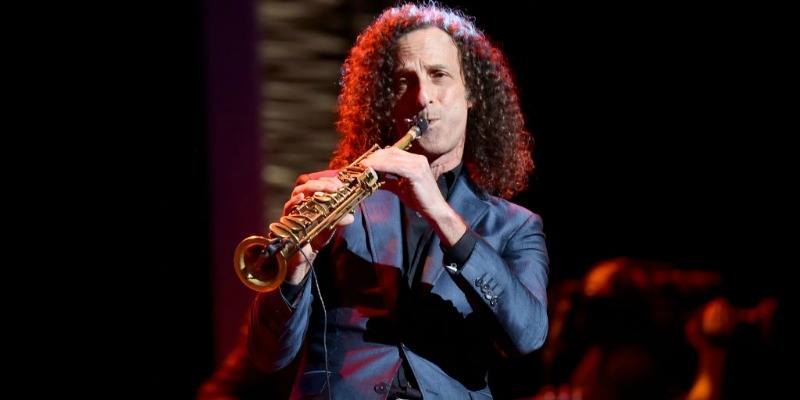 Kenny G is playing the saxophone on stage.