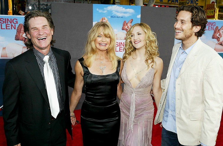 Kurt Russell, Goldie Hawn, Kate Hudson, and Oliver Hudson smiling with their arms around each other on the red carpet