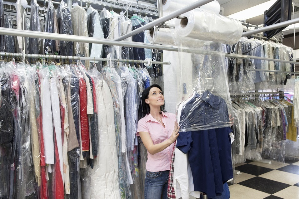 woman looking up while putting clothes in plastic
