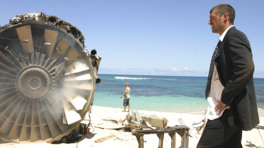 Matthew Fox in a suit, standing next to a plane engine on a beach