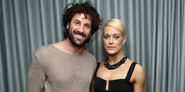 Maksim Chmerkovskiy and Peta Murgatroyd pose together with their arms around each other in front of a grey curtain.