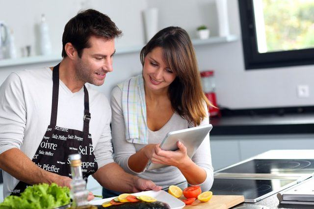 Couple in kitchen looking at an iPad.