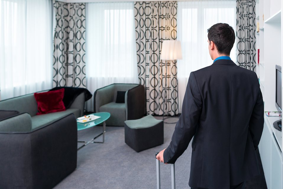man arrives in hotel room