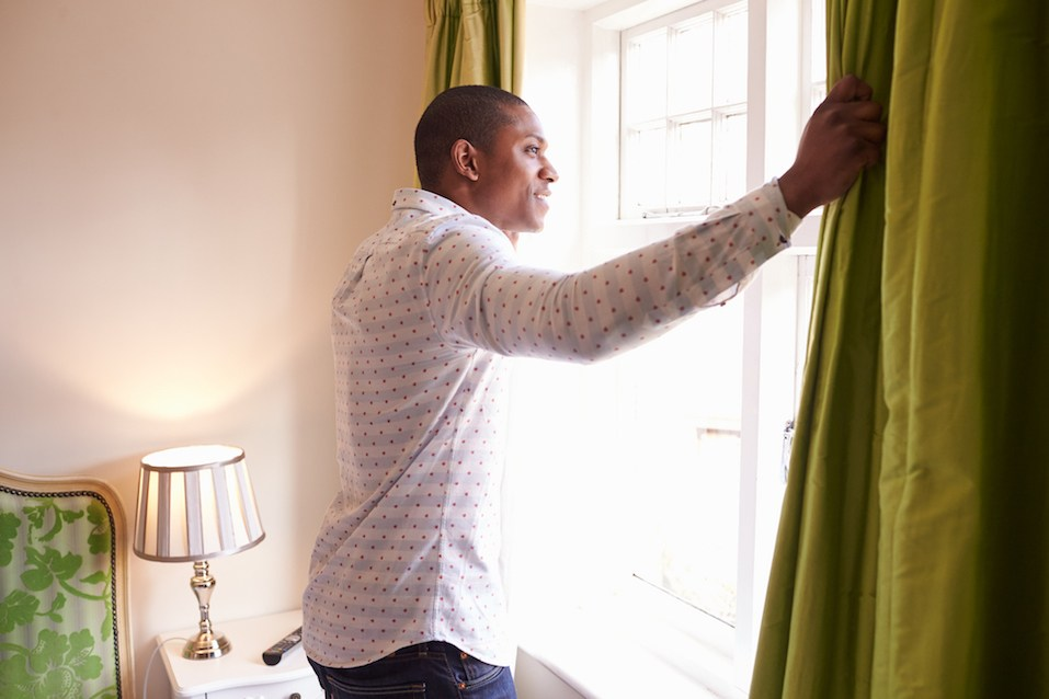 Man opens curtains
