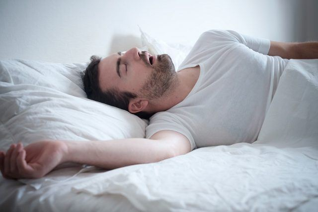 Man sleeping in his bed while snoring.