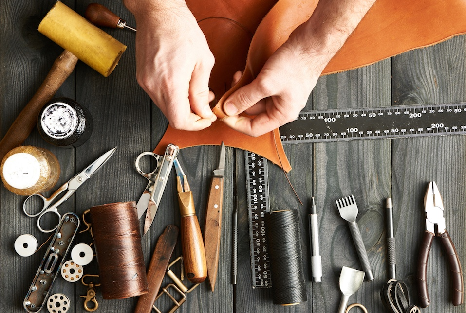 Man working with leather using crafting tools -- very old-fashioned