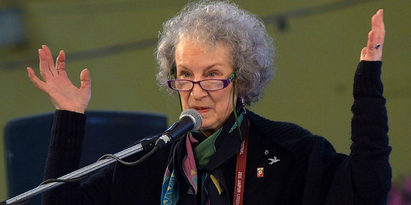 Margaret Atwood is talking at the podium and has her arms up in the air.