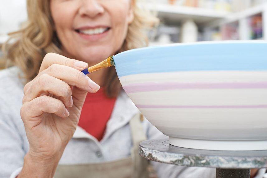 senior woman decorating bowl
