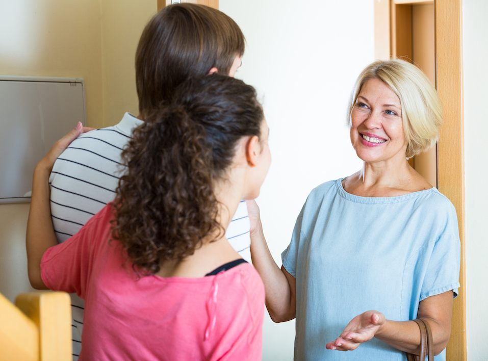 Young family couple welcoming senior mother at door and smiling