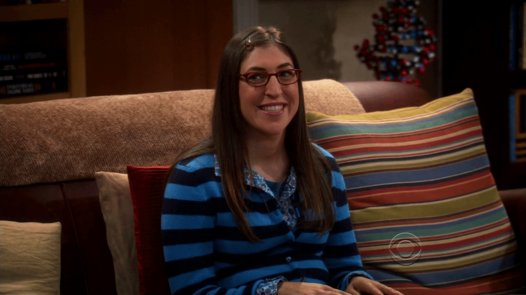 Mayim Bialick, wearing a blue striped sweater, and smiling on a couch