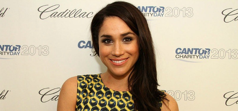 Meghan Markle is smiling in a black and yellow dress on the red carpet.