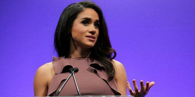 Meghan Markle is wearing a purple shirt and talking at a podium.