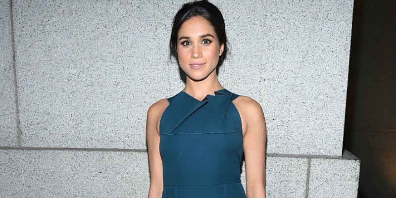 Meghan Markle is wearing a blue dress on the red carpet.
