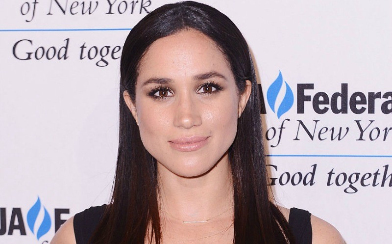 This is a closeup of Meghan Markle wearing a black dress on the red carpet.