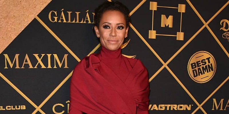 Mel B is in a dark red dress on the red carpet.
