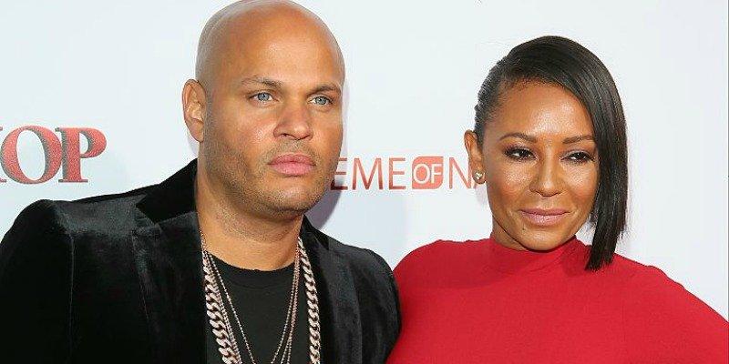 Mel B is in a red dress with Stephen Belafonte who is in a black outfit on the red carpet.
