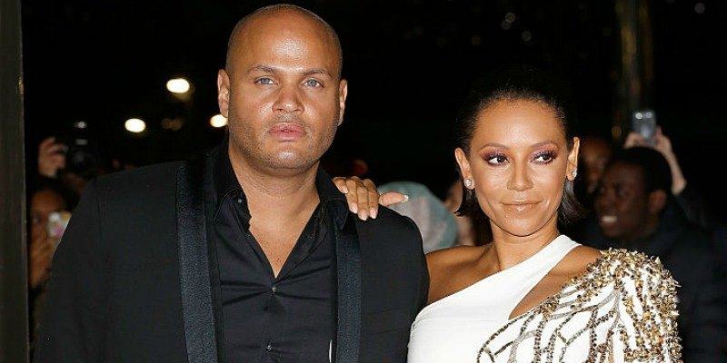 Mel B is in a white gown and Stephen Belafonte is in a black suit on the red carpet.