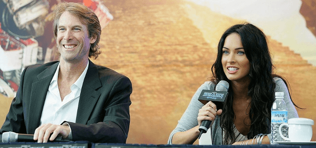 Michael Bay and Megan Fox are sitting down at a panel and smiling.