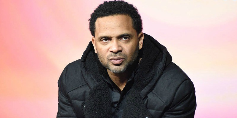 Mike Epps is in a black jacket and looks seriously ahead.