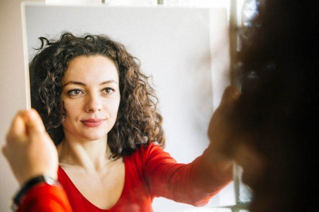 Woman with curly hair looks in the mirror.