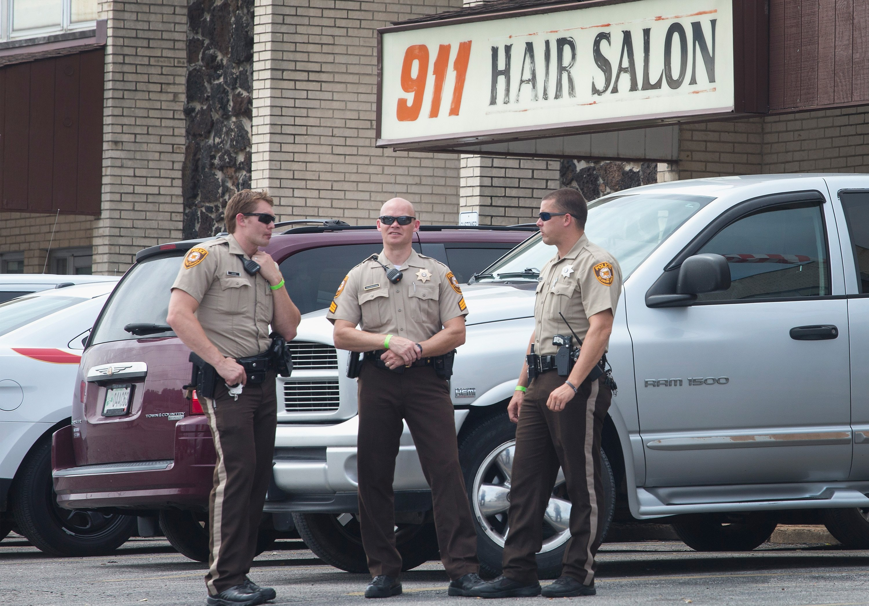 Police stand guard outside a hair salon in Ferguson