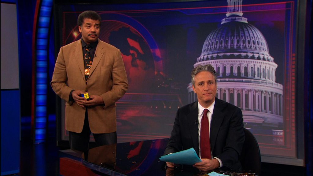 Neil Degrasse Tyson holding a Rubiks Cube, standing behind Jon Stewart on The Daily Show