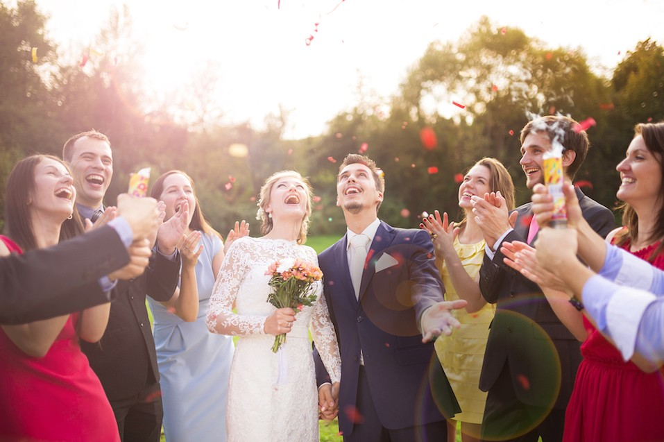 newlywed couple and their friends at the wedding party showered with confetti in green sunny park