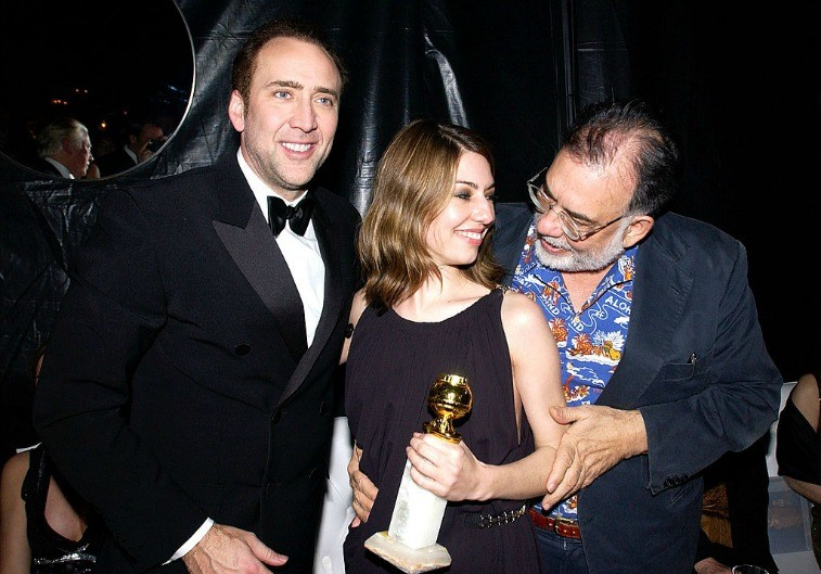 Nicolas Cage, Sofia Coppola, and Francis Ford Coppola pose for the cameras with a Golden Globe