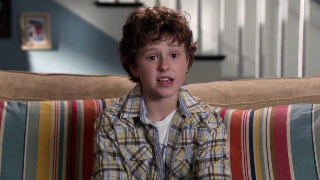 Nolan Gould, speaking directly to the camera and sitting on a couch