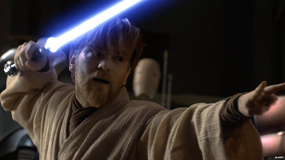 Obi Wan in live action form with his lightsaber out in front of him in the prequels