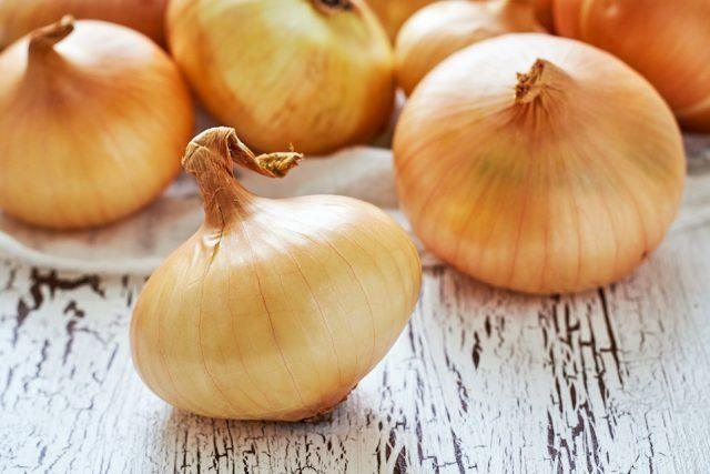 Closeup of onions on white rustic wooden background