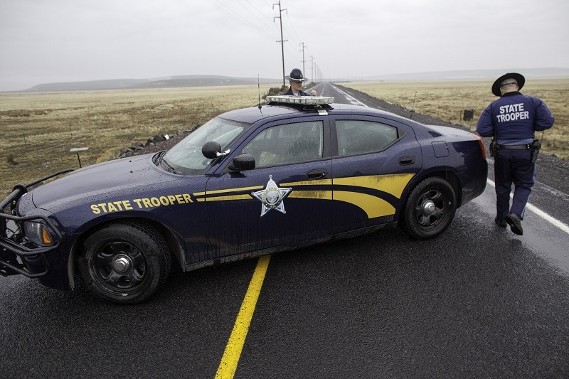 Oregon State Police officers monitor a closed area at a road checkpoint