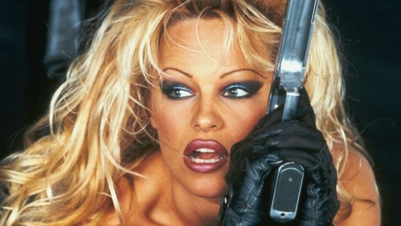 Pamela Anderson holding a gun and wearing gloves in poster art for 'Barb Wire'