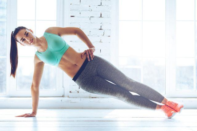 A young woman does a side plank at a gym.
