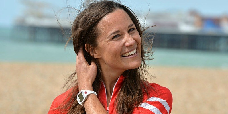 Pippa Middleton pulls her hair back as she's posing at a beach.