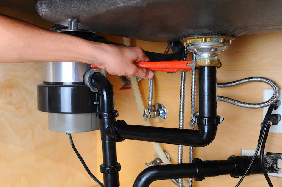 A plumber uses a wrench to tighten a fitting beneath a kitchen sink.