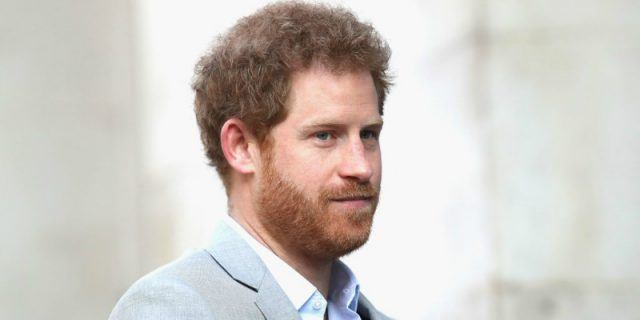 Prince Harry is in a light grey suit looking towards a crowd.