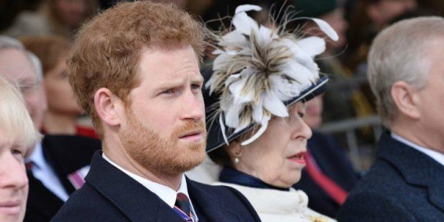 Prince Harry sits next to Queen Elizabeth II while they watch a ceremony.