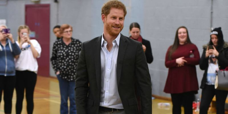 Prince Harry is smiling and wearing a suit in a gymnasium.