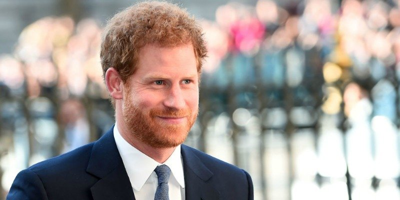 Prince Harry is smiling and in a dark suit.